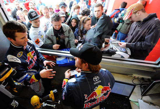 (Left to right) NASCAR Sprint Cup Series Red Bull Racing teammates Kasey Kahne and Brian Vickers talk as they sign autographs for fans in the garage area during Preseason Thunder testing on Friday at Daytona International Speedway in Daytona Beach, Fla. (Credit: Jared C. Tilton/Getty Images for NASCAR)