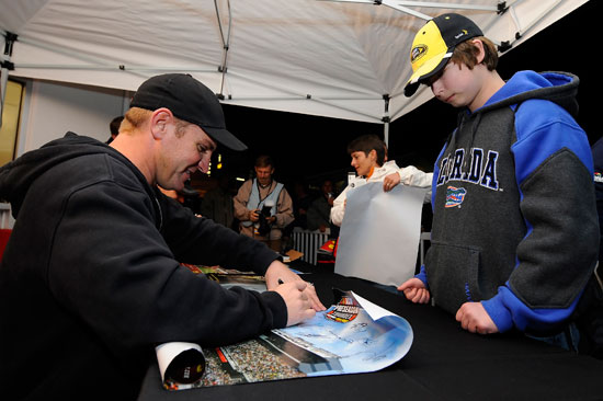 Clint Bowyer signs autographs for fans during Preseason Thunder on Friday at Daytona International Speedway in Daytona Beach, Fla. (Credit: Jared C. Tilton/Getty Images for NASCAR)