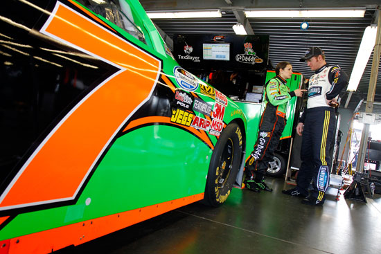 Danica Patrick talks to Dale Earnhardt Jr. about the No.7 GoDaddy.com Chevrolet in the Garage during practice at Daytona International Speedway in Daytona Beach, Fla. (Credit: Jason Smith/Getty Images for NASCAR)