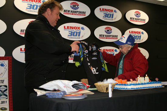 Jerry Gappens, president of New Hampshire International Speedway, presents 100-year-old Rachel Gilbert with an autographed shirt from her favorite driver Carl Edwards. (Credit: Jonathan Stallsmith)