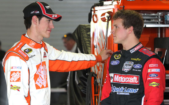 (Left to right) NASCAR Sprint Cup Series drivers Joey Logano and Trevor Bayne talk in the garage during practice Friday at Talladega Superspeedway in Talladega, Ala. (Credit: Jerry Markland/Getty Images for NASCAR)