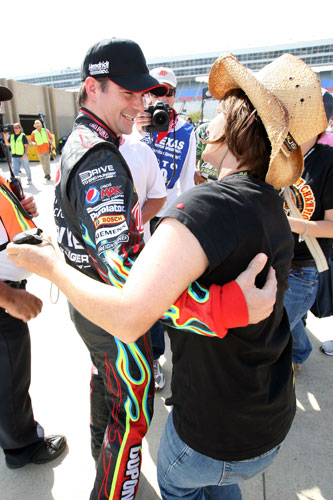Jeff Gordon, driver of the No. 24 DuPont Chevrolet, hugs a fan in the garage area during practice for the NASCAR Sprint Cup Series Samsung Mobile 500 at Texas Motor Speedway on Apr. 7 in Fort Worth, Texas. (Credit: Jerry Markland/Getty Images for NASCAR)
