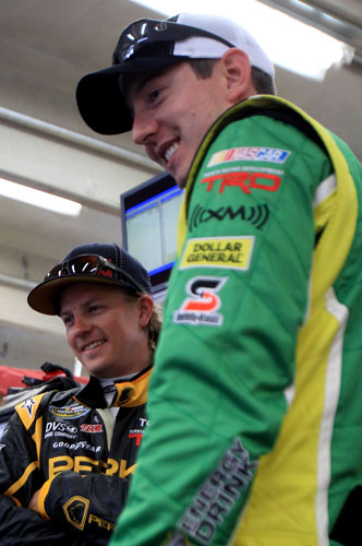 Kimi Raikkonen, driver of the No. 15 Perky Jerky Toyota, stands with Kyle Busch, driver of the No. 18 NOS Energy Drink Toyota, in the garage area during practice for the NASCAR Camping World Truck Series North Carolina Education Lottery 200 at Charlotte Motor Speedway on May 20 in Charlotte, N.C. (Credit: Streeter Lecka, Getty Images for NASCAR)