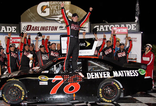Regan Smith climbs out of the No.78 Furniture Row Chevrolet after winning the Showtime Southern 500 at Darlington Raceway. (Credit: Geoff Burke/Getty Images for NASCAR)