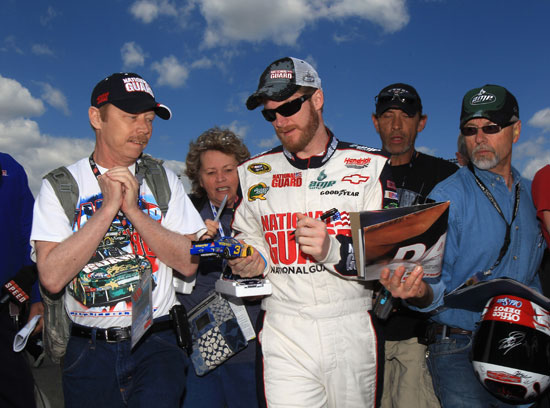Dale Earnhardt Jr., driver of the No. 88 National Guard/Amp Energy Chevrolet, signs autographs in the garage area during practice for the NASCAR Sprint Cup Series Crown Royal Presents The Matthew and Daniel Hansen 400 at Richmond International Raceway on Apr. 29 in Richmond, Va. (Credit: Streeter Lecka/Getty Images)