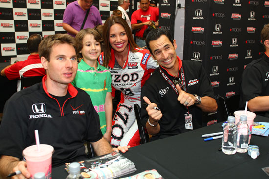 Will Power and Helio Castroneves pose for photos with a young fan at a autograph signing event