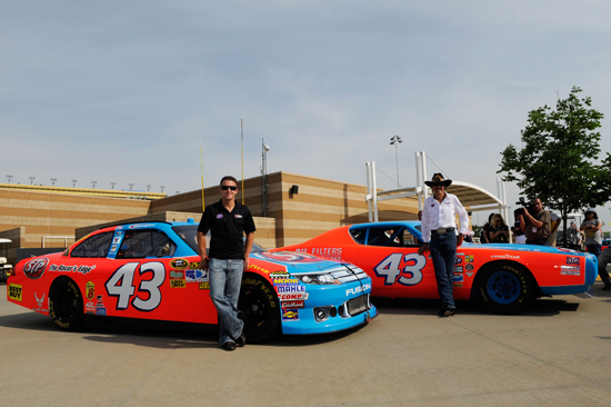 (Left to right) AJ Allmendinger stands next to his 2011 NASCAR Sprint Cup Series car as NASCAR Hall of Famer Richard Petty stands beside his iconic STP ride as the sponsor returns to the sport on Friday at Kansas Speedway in Kansas City, Kan. (Credit: John Harrelson/Getty Images for NASCAR)