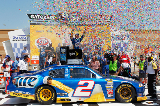 Brad Keselowski climbs out of the No. 2 Miller Lite Dodge in victory lane after winning the STP 400 (Credit: Geoff Burke/Getty Images for NASCAR)