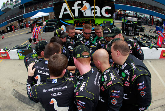 The No. 99 pit crew of Carl Edwards huddles before the start of the Heluva Good Sour Cream Dips 400 at Michigan International Speedway. (Credit: Tom Pennington/Getty Images)