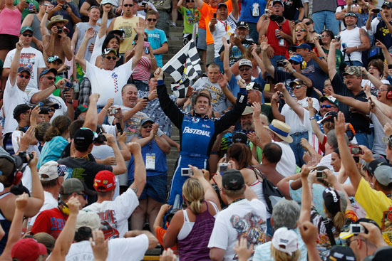 Carl Edwards climbs into the Michigan International Speedway grandstands to celebrate his Alliance Truck Parts 250 victory with the fans. (Credit: Chris Graythen/Getty Images)