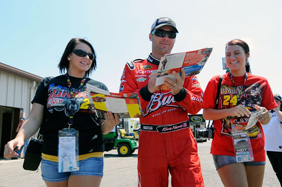 Kevin Harvick signs autographs for fans as he walks through the garage with them on Friday at Michigan International Speedway. (Credit: Jared C. Tilton/Getty Images for NASCAR)