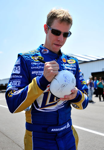 Brad Keselowski, driver of the No. 2 Miller Lite Dodge, signs an autograph in the garage area during practice for the 5-Hour Energy 500 at Pocono Raceway on June 10 in Long Pond, Pa. (Credit: Jason Smith/Getty Images)