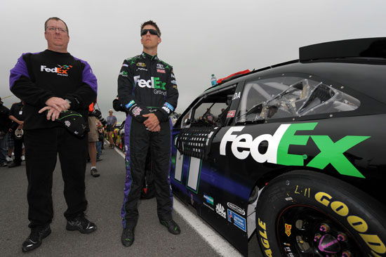 Denny Hamlin and crew chief Mike Ford stand by the No. 11 FedEx Toyota during pre-race activities for the 5-Hour Energy 500 at Pocono Raceway. (Credit: Drew Hallowell/Getty Images for NASCAR)