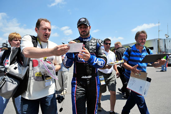 Jimmie Johnson, driver of the No. 48 Lowe's Chevrolet, signs an autograph during practice for the 5-Hour Energy 500 at Pocono Raceway on June 10 in Long Pond, Pa. (Credit: Jason Smith/Getty Images)