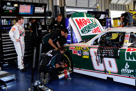 Dale Earnhardt Jr., driver of the No. 88 Diet Mountain Dew/National Guard Chevrolet, stands in front of his car in the garage as crew members work on the car during testing for the NASCAR Sprint Cup Series at Kentucky Speedway on July 7 in Sparta, Ky. (Credit: John Harrelson/Getty Images for NASCAR)