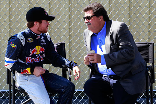 Brian Vickers (left), driver of the No. 83 Red Bull Toyota, talks with NASCAR President Mike Helton (right) in the garage during practice for the NASCAR Sprint Cup Series LENOX Industrial Tools 301 at New Hampshire Motor Speedway on July 15 in Loudon, N.H. (Credit: Chris Trotman/Getty Images)