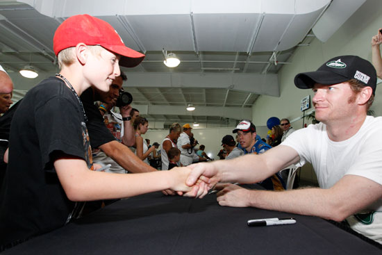 Dale Earnhardt Jr., driver of the No. 88 AMP Energy/National Guard Chevrolet, signs an autograph for a race fan at the largest 2011 NASCAR Sprint Cup Series autograph session held at Indianapolis Motor Speedway on July 30 in Indianapolis, Ind. (Credit: Getty Images for NASCAR)