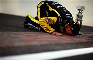 Paul Menard, driver of the #27 NIBCO/Menards Chevrolet, poses as he kisses the bricks after winning the NASCAR Sprint Cup Series Brickyard 400 at Indianapolis Motor Speedway on July 31, 2011 in Indianapolis, Indiana. (Photo by Tom Pennington/Getty Images for NASCAR) photo