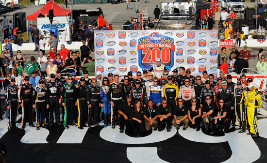 The starting lineup of drivers pose with the staff from Lucas Oil Raceway during pre-race activities for the NASCAR Nationwide Series Kroger 200 at Lucas Oil Raceway on July 30 in Indianapolis, Ind. (Credit: Jason Smith/Getty Images for NASCAR)