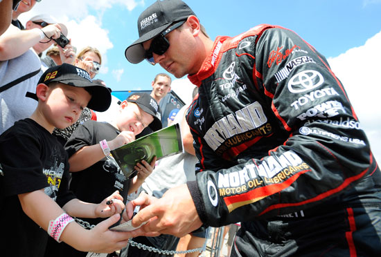 Michael Annett, driver of the No. 62 Northland Motor Oils Toyota signs autographs for young fans during qualifying for the NASCAR Nationwide Series U.S. Cellular 250 at Iowa Speedway on Aug. 6 in Newton, Iowa. (Credit: Jason Smith/Getty Images for NASCAR)