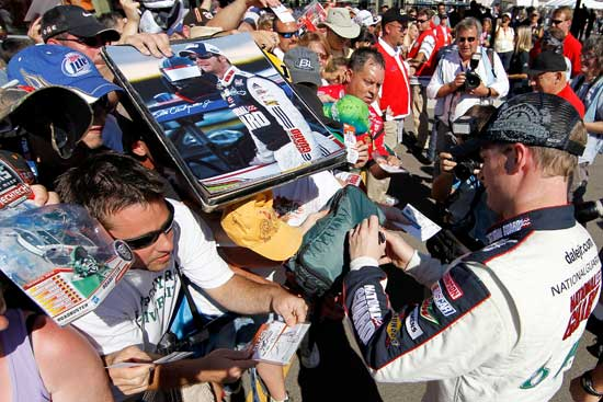Dale Earnhardt Jr. (right), driver of the No. 88 National Guard/Amp Energy Chevrolet, signs autographs for fans after qualifying for the NASCAR Sprint Cup Series Pure Michigan 400 at Michigan International Speedway on Aug. 19 in Brooklyn, Mich. (Credit: Wesley Hitt/Getty Images for NASCAR)