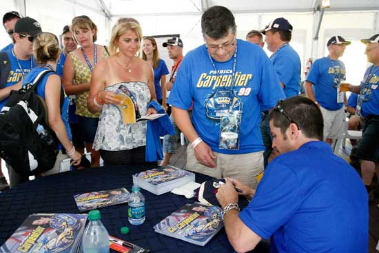Patrick Carpentier of the No. 99 NAPA Auto Parts Toyota signs autographs for fans prior to the NAPA Auto Parts 200 at Circuit Gilles Villeneuve on Aug. 20 in Montreal, Quebec, Canada. (Credit: Richard Wolowicz/Getty Images)