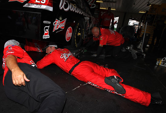 Kevin Harvick, driver of the No. 29 Budweiser Chevrolet, looks under his car during practice for the NASCAR Sprint Cup Series Good Sam RV Insurance 500 at Pocono Raceway on Aug. 5 in Long Pond, Pa. (Credit: Nick Laham/Getty Images)