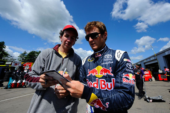Kasey Kahne (right), driver of the No. 4 Red Bull Toyota, signs his autograph for a fan in the garage area during practice for the NASCAR Sprint Cup Series Heluva Good! Sour Cream Dips at the Glen at Watkins Glen International on Aug. 12 in Watkins Glen, N.Y. (Credit: Jason Smith/Getty Images for NASCAR)
