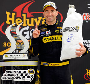 Marcos Ambrose, driver of the No. 9 Stanley Ford, poses in Victory Lane after winning the NASCAR Sprint Cup Series Heluva Good! Sour Cream Dips at the Glen at Watkins Glen International on Aug. 15 in Watkins Glen, N.Y. (Credit: Jason Smith/Getty Images for NASCAR)