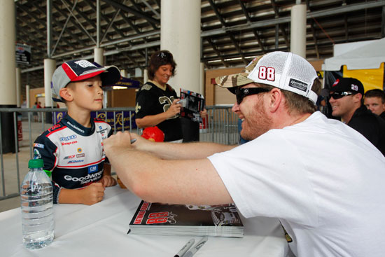 NASCAR Sprint Cup Series driver Dale Earnhardt Jr. signs an autograph for a young fan at Atlanta Motor Speedway on Sept. 2 in Hampton, Ga. (Credit: By Geoff Burke/Getty Images for NASCAR)