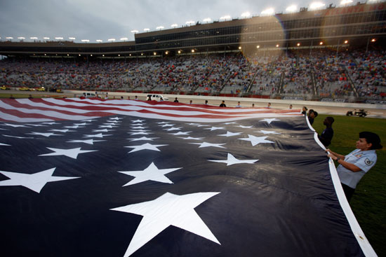 The American flag is displayed by U.S. service members during pre-race ceremonies for the NASCAR Sprint Cup Series AdvoCare 500 at Atlanta Motor Speedway on Sept. 4 in Hampton, Ga. (Credit: Chris Graythen/Getty Images)
