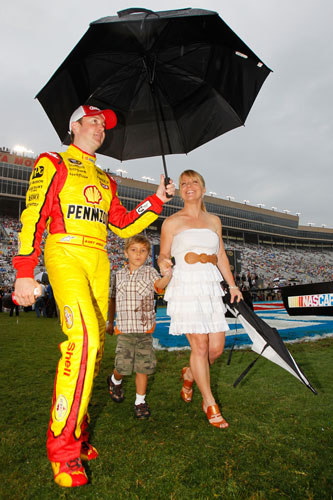 Kurt Busch, driver of the No. 22 Shell/Pennzoil Dodge, walks with his girlfriend, Patricia Driscoll, and her son, Houston, during driver introductions prior to the NASCAR Sprint Cup Series AdvoCare 500 at Atlanta Motor Speedway on Sept. 4 in Hampton, Ga. (Credit: Todd Warshaw/Getty Images)