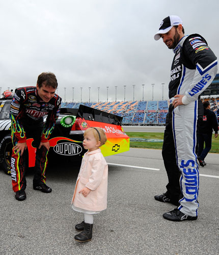 Jeff Gordon (left) and Jimmie Johnson (right) look after Genevieve Marie, Johnson's daughter, on the grid prior to the NASCAR Sprint Cup Series GEICO 400 at Chicagoland Speedway on Sept 19 in Joliet, Ill. (Credit: Jason Smith/Getty Images)