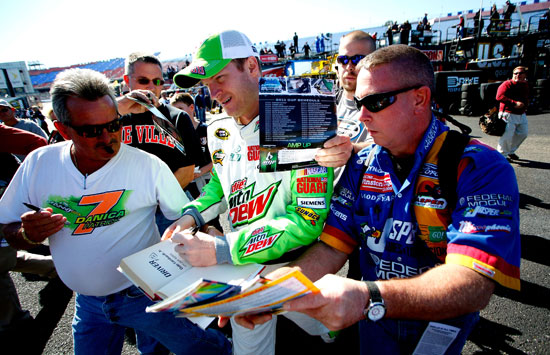Dale Earnhardt Jr., driver of the No. 88 Diet Mountain Dew Chevrolet, signs autographs for fans during practice for the NASCAR Sprint Cup Series Good Sam Club 500 at Talladega Superspeedway on Oct. 21 in Talladega, Ala. (Credit: Jeff Zelevansky/Getty Images for NASCAR)
