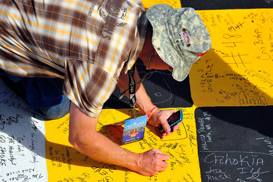 A fan signs the start/finish line prior to the start of the Good Sam Club 500 at Talladega Superspeedway. (Credit: Jason Smith/Getty Images for NASCAR)