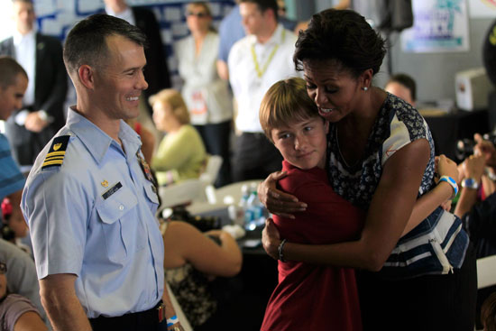 First Lady Michelle Obama hugs a child as she greets military families at a Joining Forces pre-race event at Homestead-Miami Speedway on Sunday, Nov. 20. (Credit: By Chris Trotman, Getty Images for NASCAR)
