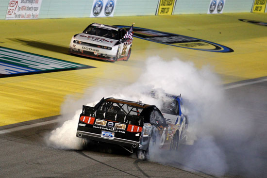 Ricky Stenhouse Jr. (6) and teammate Carl Edwards perform a head-to-head burnout in celebration of Stenhouse's NASCAR Nationwide Series title while race winner Brad Keselowski celebrates in the background at Homestead-Miami Speedway on Saturday, Nov. 19.