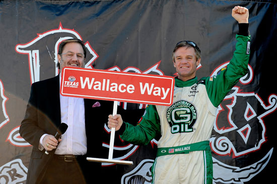 Kenny Wallace, driver of the #09 G-Oil Toyota, is congratulated on stage by Texas Motor Speedway President Eddie Gossage on his 520th NASCAR Nationwide Series race in the O&#039;Reilly Auto Parts Challenge at Texas Motor Speedway on Nov. 5, 2011, in Fort Worth, Texas. (Credit: Jared C. Tilton/Getty Images for NASCAR)