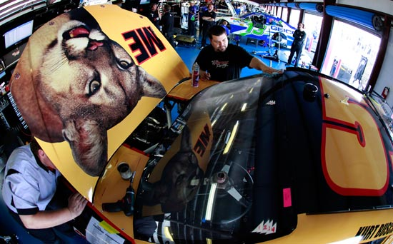 "Crew members work on the No. 51 Phoenix Construction Services Chevrolet of Kurt Busch that is sporting a special ""Talladega Nights"" paint scheme. (Credit: Tom Pennington/Getty Images for NASCAR)"