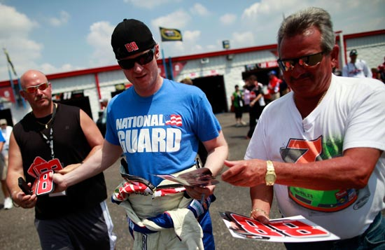 A freshly-shaved Dale Earnhardt Jr. signs autographs in the Talladega Superspeedway garage. (Credit: Tom Pennington/Getty Images for NASCAR)