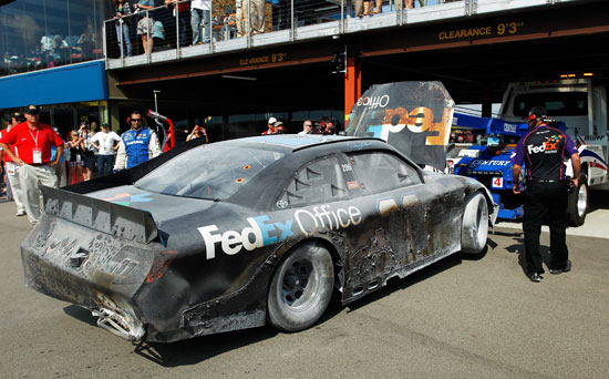 The No. 11 FedEx Office Toyota of Denny Hamlin is towed into the garage area after an incident during the NASCAR Sprint Cup Series Quicken Loans 400 at Michigan International Speedway on Sunday in Brooklyn, Mich. (Credit: Wesley Hitt/Getty Images for NASCAR)