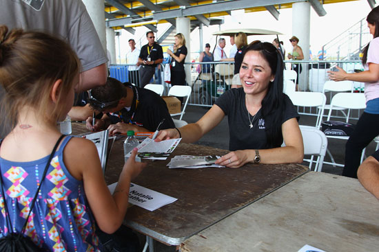 Natalie Sather signs an autograph for a fan before the American Ethanol 200 at Iowa Speedway. (Credit: Dilip Vishwanat/Getty Images)