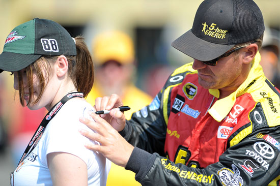 Clint Bowyer signs an autograph during qualifying for the LENOX Industrial Tools 301 at New Hampshire Motor Speedway. (Credit: Drew Hallowell/Getty Images for NASCAR)