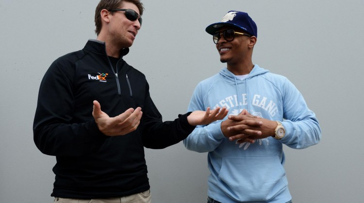 Denny Hamlin (L), driver of the #11 FedEx Express Toyota, talks to Rapper Clifford 'T.I.' Harris during the NASCAR Sprint Cup Series Daytona 500 at Daytona International Speedway on February 24, 2013 in Daytona Beach, Florida. (Credit: John Harrelson/Getty Images for NASCAR)