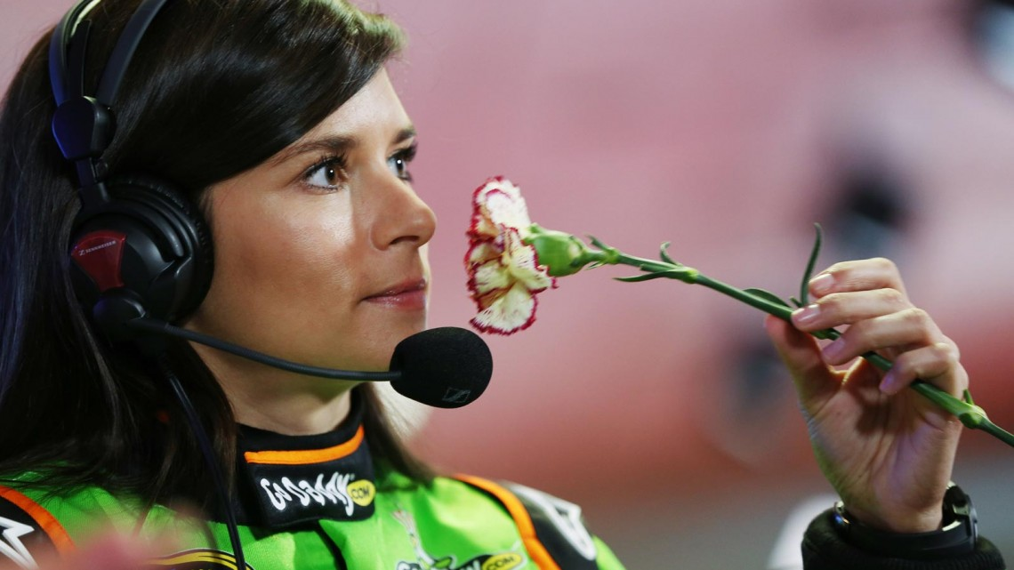 Driver Danica Patrick smells a flower during the 2013 NASCAR media day at Daytona International Speedway on February 14, 2013 in Daytona Beach, Florida. (Photo by Tom Pennington/NASCAR via Getty Images)