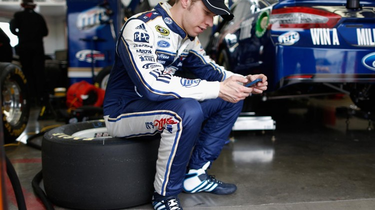 Brad Keselowski, driver of the #2 Miller Lite Ford checks his phone in the garage area during NASCAR Sprint Cup Series testing at Las Vegas Motor Speedway on March 7, 2013 in Las Vegas, Nevada. (Credit: Chris Graythen/Getty Images)