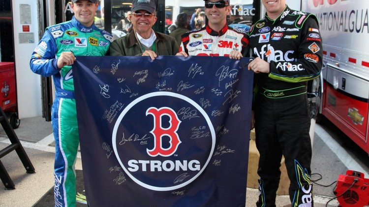 Ricky Stenhouse Jr., driver of the #17 Zest Ford, team owner Jack Roush, Greg Biffle, driver of the #16 ACE Brand Ford, and Carl Edwards, driver of the #99 Aflac Ford, hold a banner in support of the Boston Marathon attack victims during practice for the NASCAR Sprint Cup Series STP 400 at Kansas Speedway on April 19, 2013 in Kansas City, Kansas. (Photo by Ed Zurga/Getty Images)