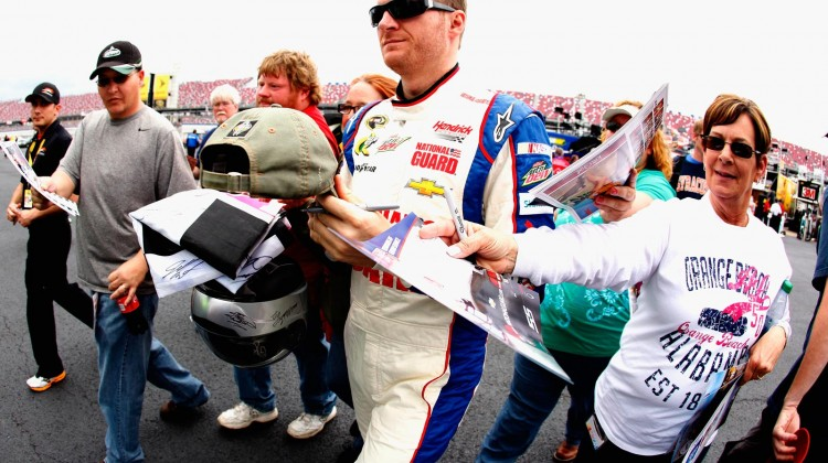 Dale Earnhardt Jr., driver of the #88 National Guard Chevrolet, signs autographs for fans during practice for the NASCAR Sprint Cup Series Aaron's 499 at Talladega Superspeedway on May 3, 2013 in Talladega, Alabama. (Credit: Sean Gardner/Getty Images)