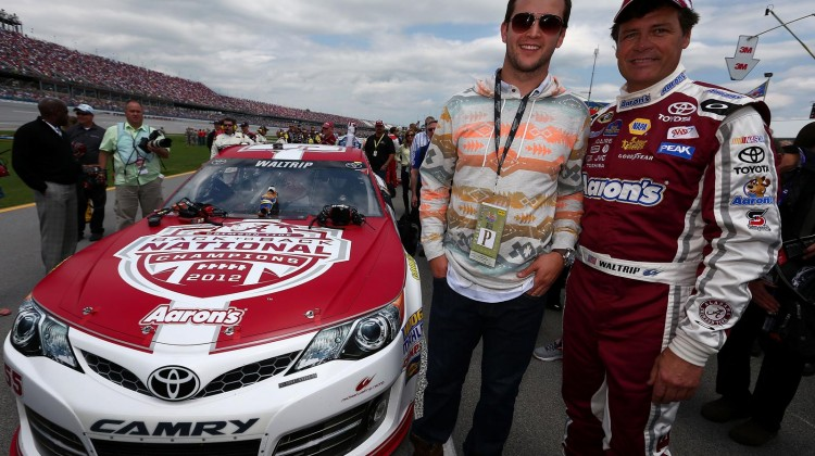 (L-R) University of Alabama quarterback AJ McCarron and Michael Waltrip, driver of the #55 Aaron's Dream Machine / Alabama National Championship Toyota, pose for a photo on the grid prior to the start of the NASCAR Sprint Cup Series Aaron's 499 at Talladega Superspeedway on May 5, 2013 in Talladega, Alabama. (Credit: Tom Pennington/NASCAR via Getty Images)