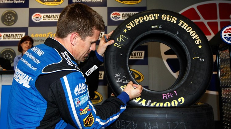 Carl Edwards, driver of the #99 Fastenal Ford, signs a 'Support our Troops' Good Year tire during a press conference in the media center at Charlotte Motor Speedway on May 23, 2013 in Concord, North Carolina. (Photo by Chris Trotman/NASCAR via Getty Images)